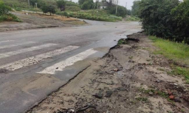 На окраине города дождь подмывает дорожное покрытие фото